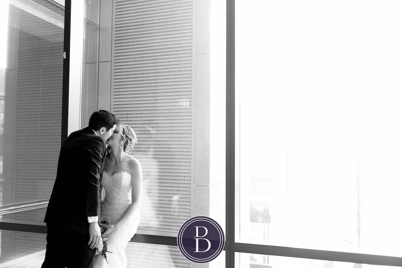 Bride and groom kiss portrait at Hydro Winnipeg building