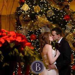 Bride and groom kiss by Christmas tree