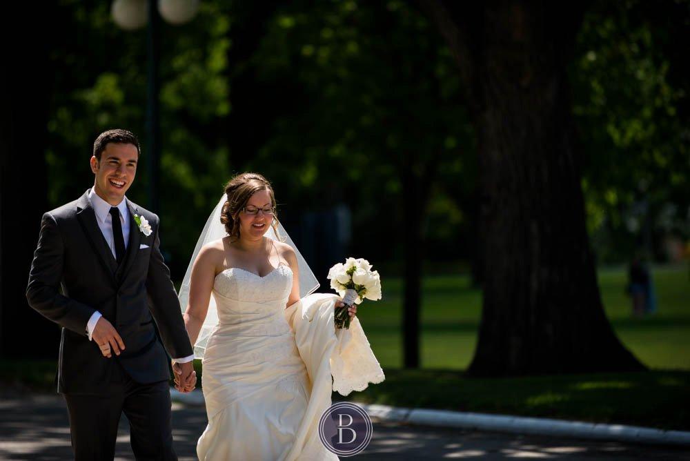 Bride and groom walking and smiling during formal photos Manitoba legislative building in Winnipeg