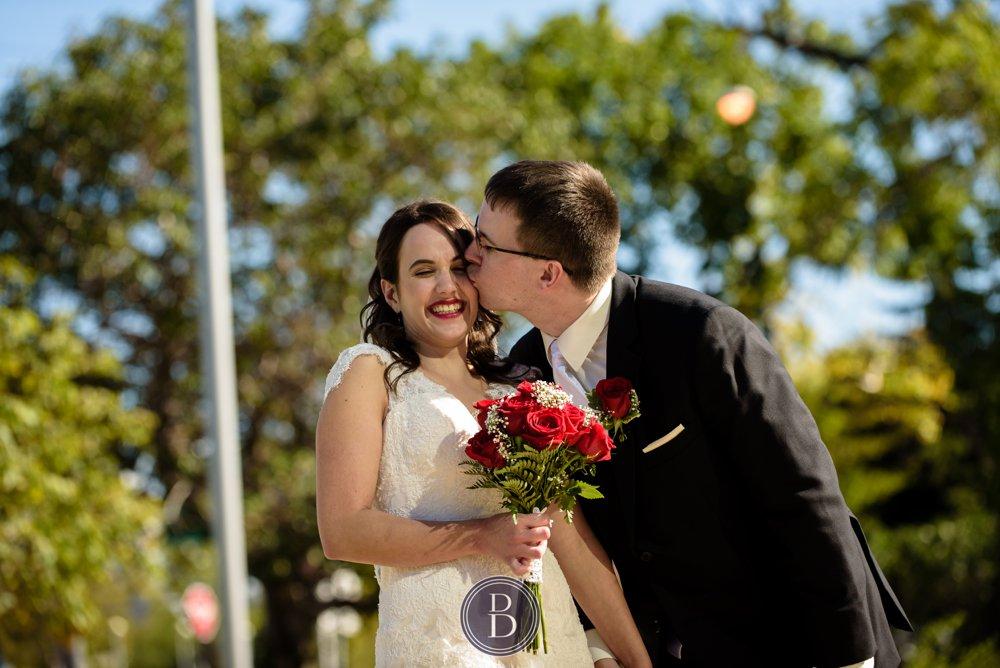 Winnipeg Wedding Photos Manitoba groom kissing bride on cheek as she smiles