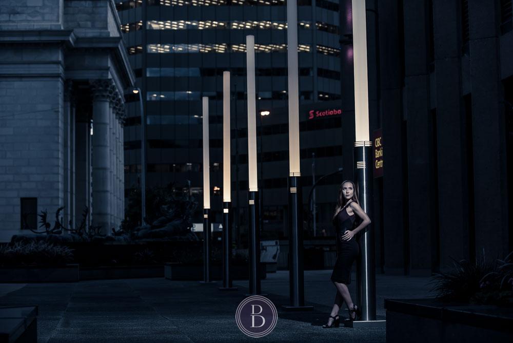 model in evening portrait by light posts downtown Winnipeg
