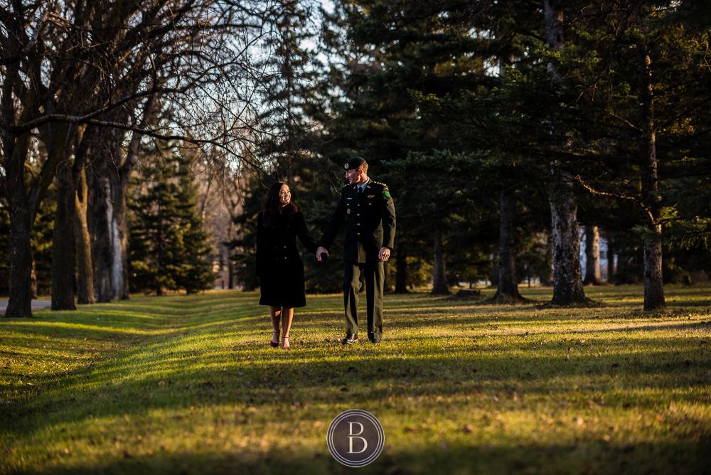 Engaged couple walking sunset Assiniboine park