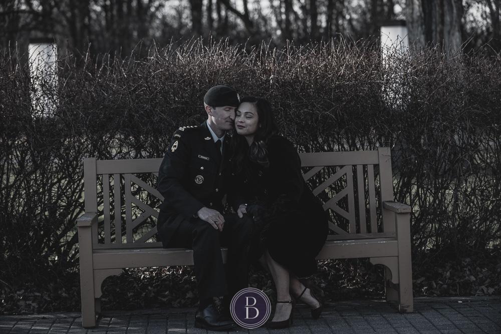 Engaged Winnipeg couple sitting on bench Assiniboine Park