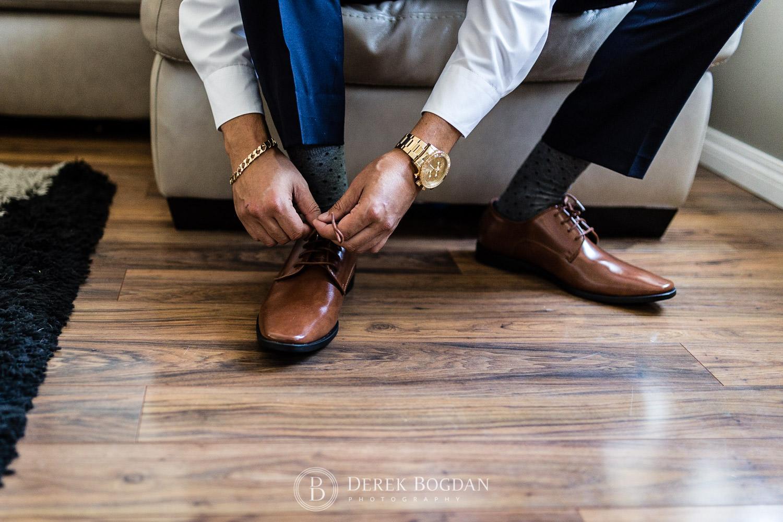 Groom putting on shoes Winnipeg wedding