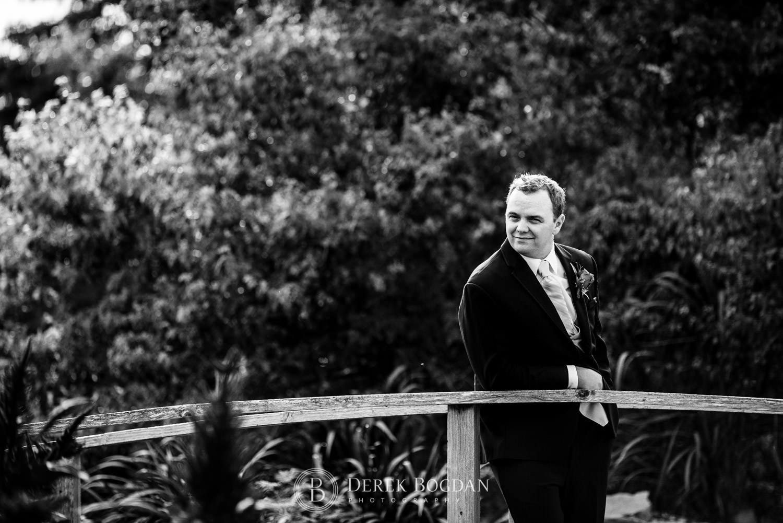 groom outdoor portrait on bridge