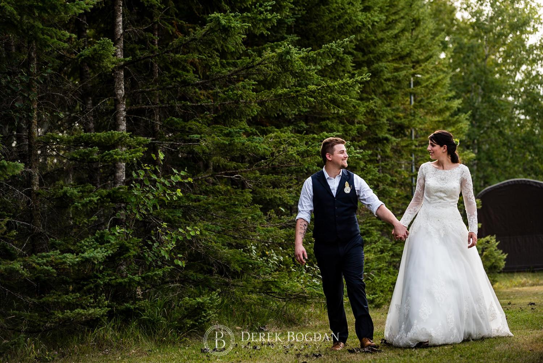 bride and groom holding hands xoutdoor ceremony Manitoba wedding