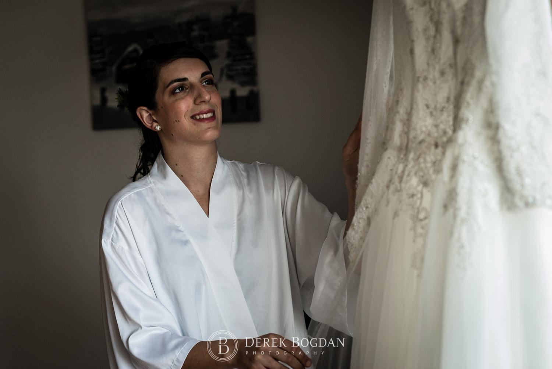 bride smiles looking at bridal dress