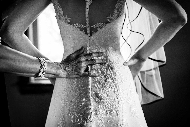 bridal back dress getting help from mom Evergreen Village Wedding Niverville Manitoba