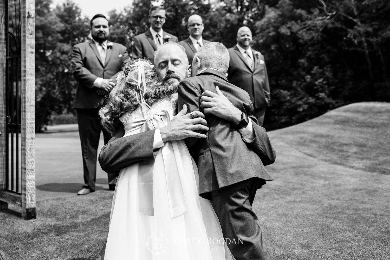 Bel Acres Golf wedding Manitoba groom hugging kids during ceremony