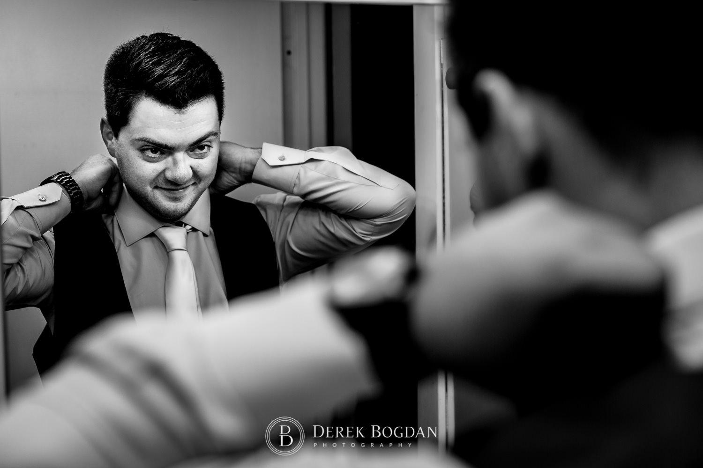 Groom getting ready looking in mirror