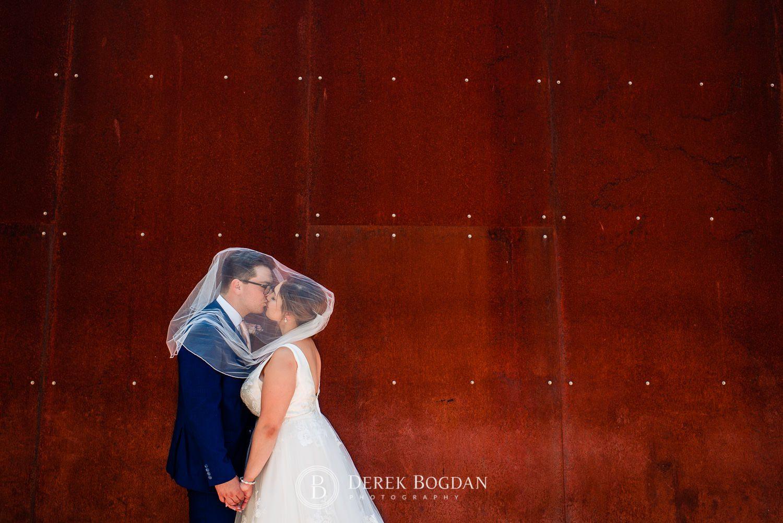 Bride and groom portrait veil kiss Qualico Family Centre