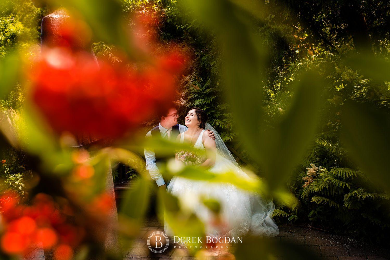 Bride and groom laughter on bench Leo Mol Sculpture Garden