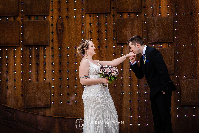 Manitoba Club Wedding post ceremony outdoor portrait groom kissing brides hand